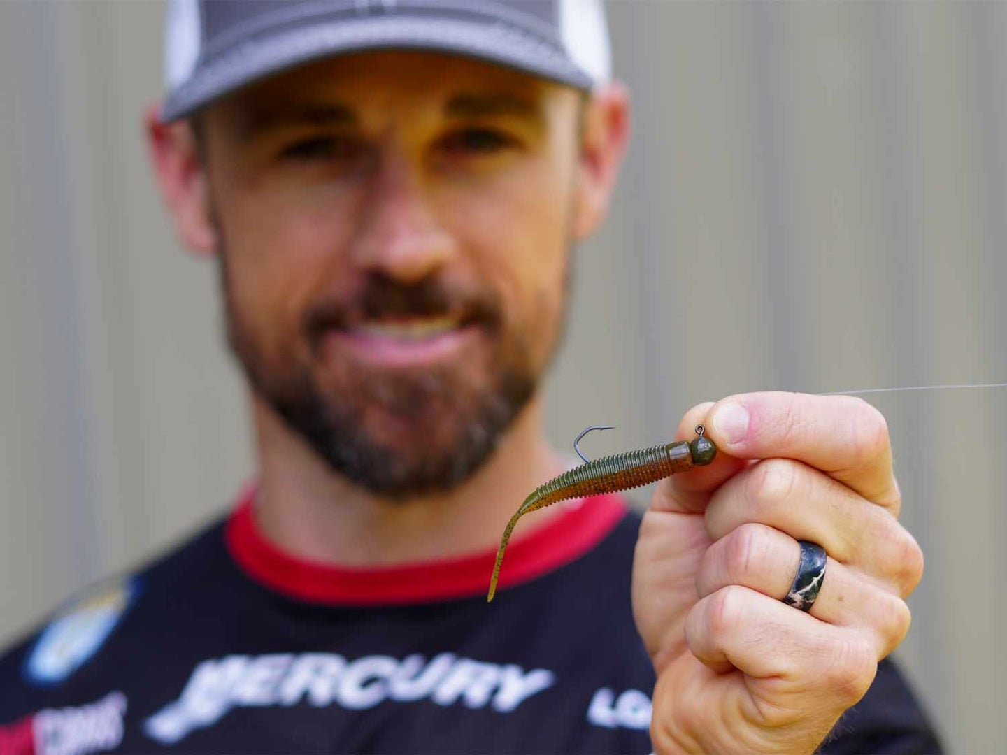 A bass fishing angler holding up his favorite fishing ned rig.