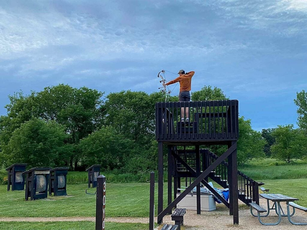 A bowhunter on a elevated shooting stand.