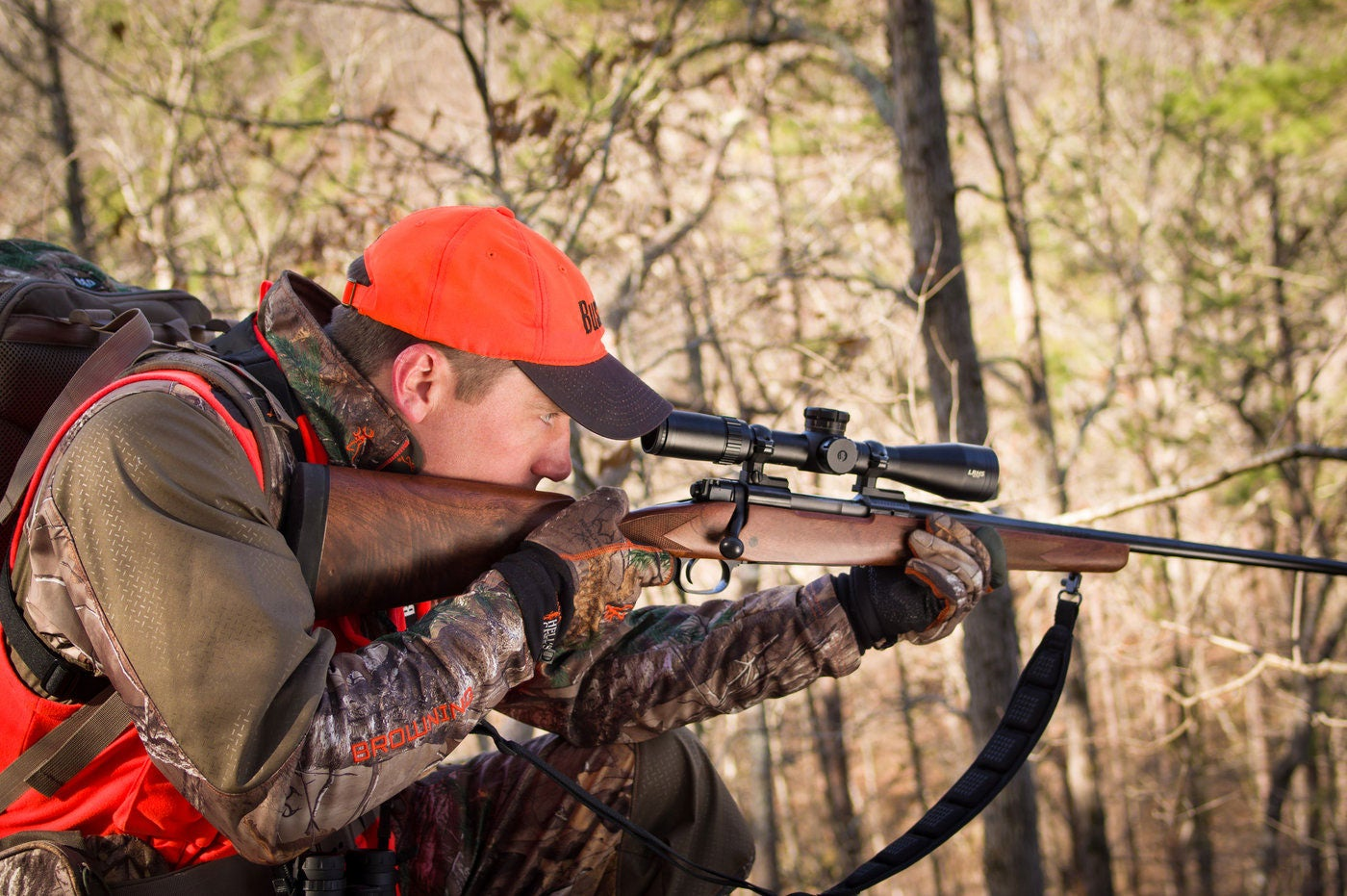 A hunter aiming a rifle in the woods.