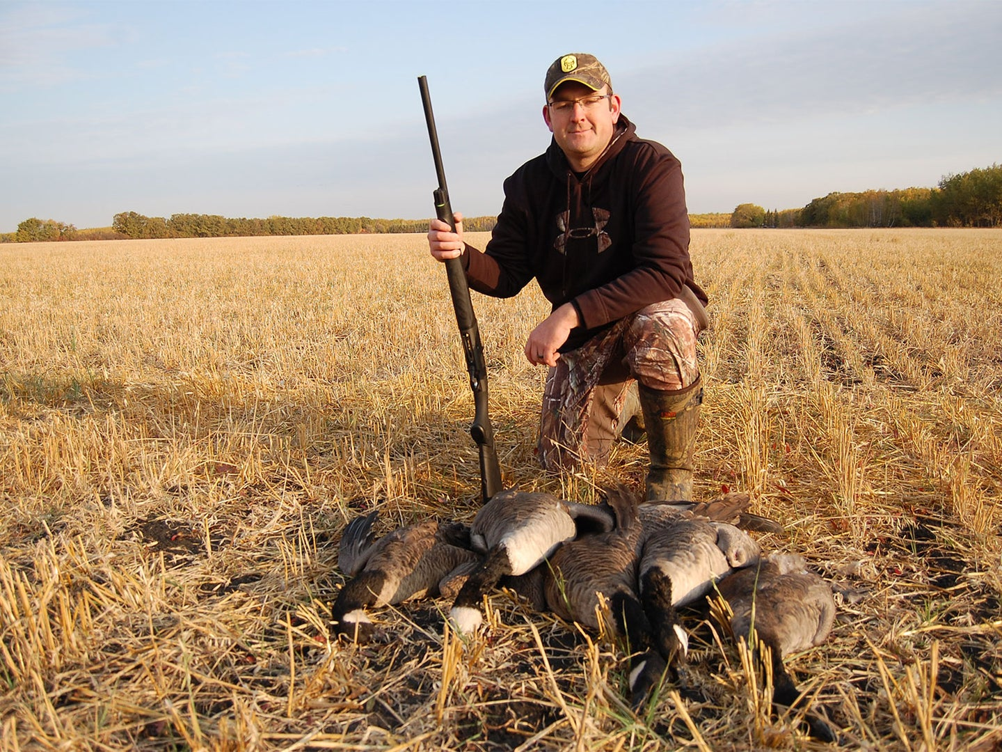 A hunter kneeling beside a limit of Canada geese.