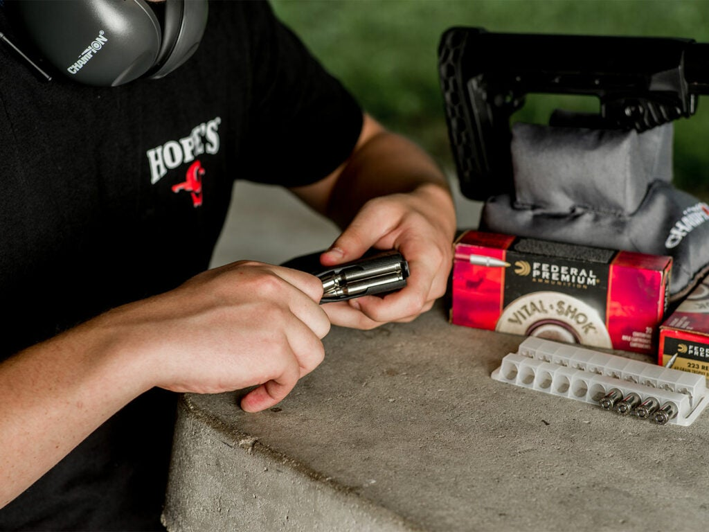 A hand reloading an ammunition clip for a handgun