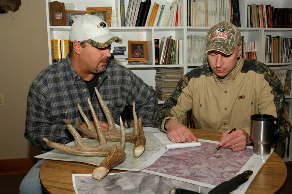 Two hunters look over maps for scouting deer.
