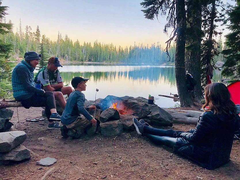 family sitting near fire