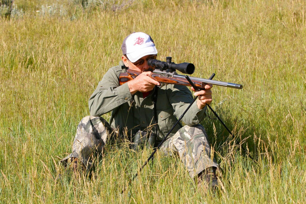 A man sitting in tall grass while aiming a rifle using a shooting stick.