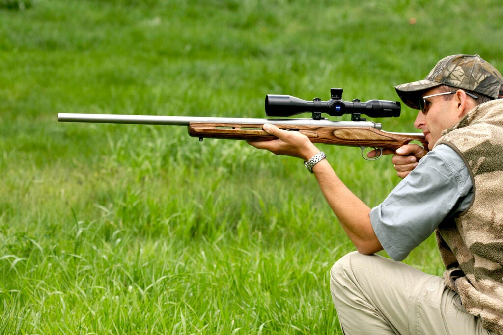A man kneeling in the grass while aiming a rifle.