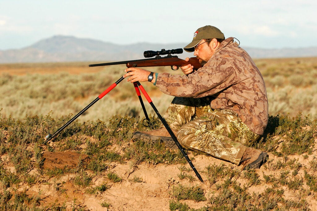 A man using a tripod to aim a rifle.