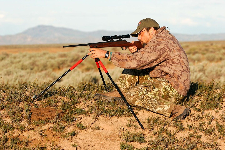 A man using a tripod to aim a rifle.