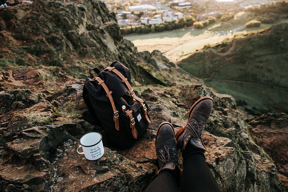 person with hiking boots on top of a mountain