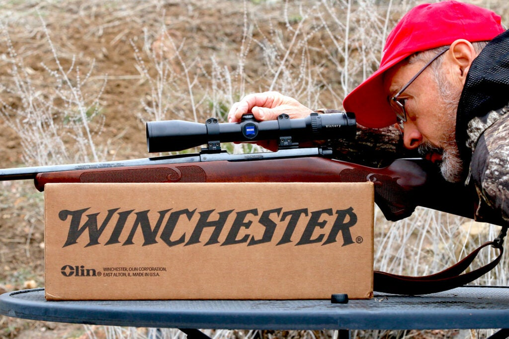 Man sighting a rifle and rifle scope on a winchester box.