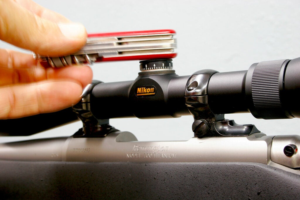 Hand using a swiss army knife on a rifle scope.