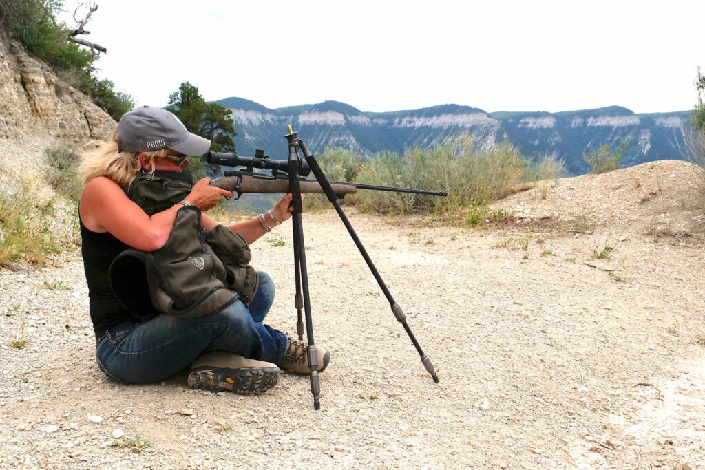 A woman using a tripod to aim a rifle.