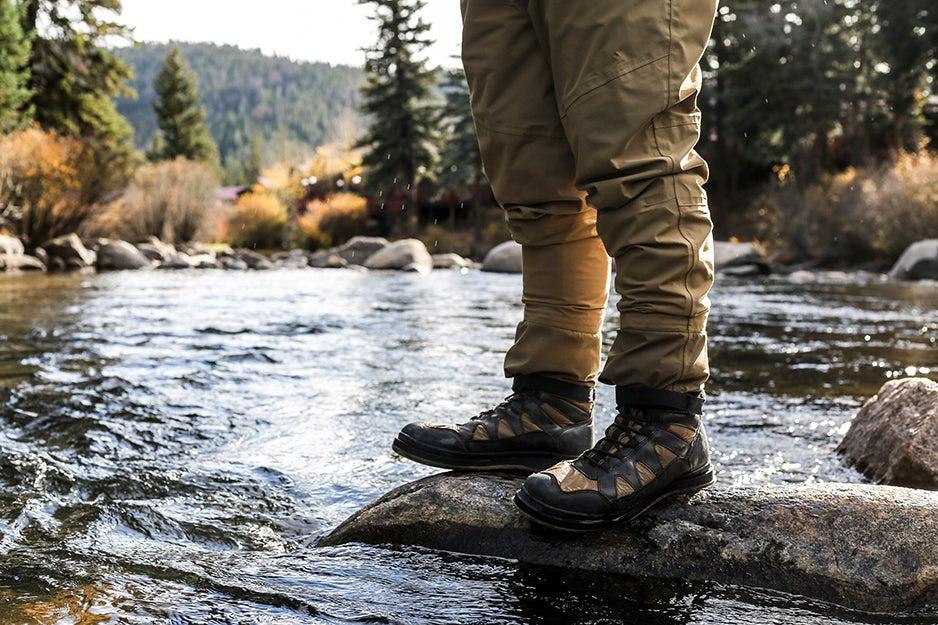 person near stream in boots