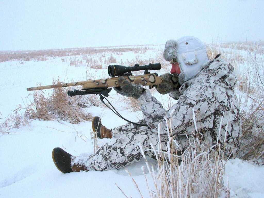 A man sitting in the snow and aiming a rifle.