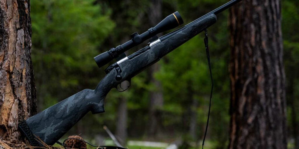 A weatherby hunting rifle propped up against a tree.