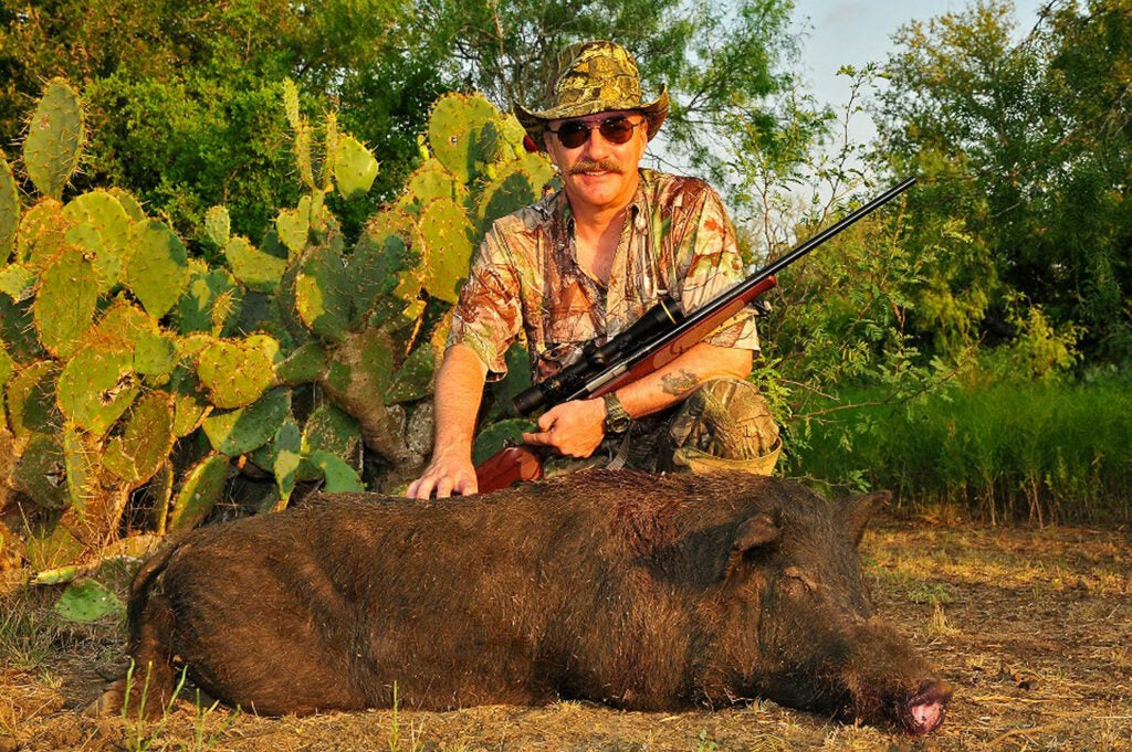 A hunter kneeling behind a dead hog.