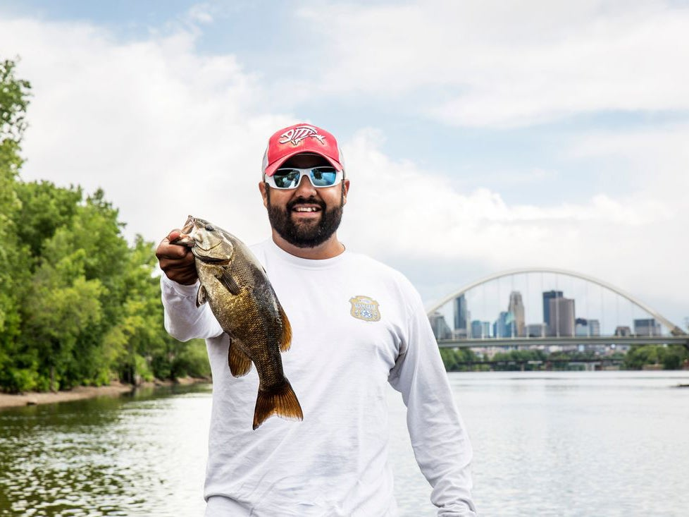A man holding up a largemouth bass with a city in the background.