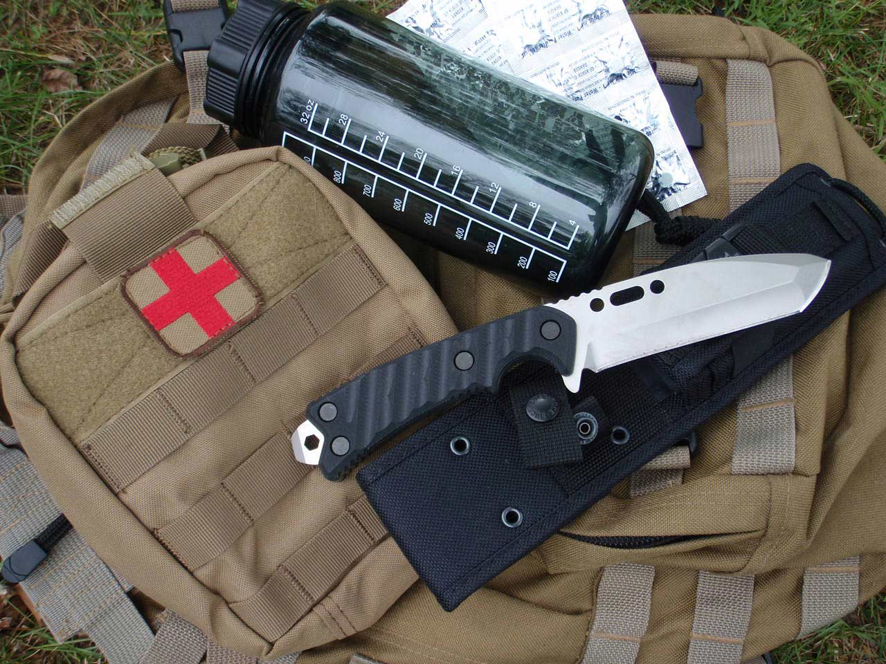 A knife and a water bottle on a survival backpack.