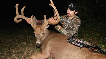 A hunter kneeling behind and holding the antlers of a large buck.