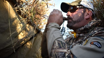 A hunter using a bird call in a hunting blind.