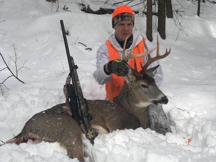A deer hunter kneeling in the snow with a deer.