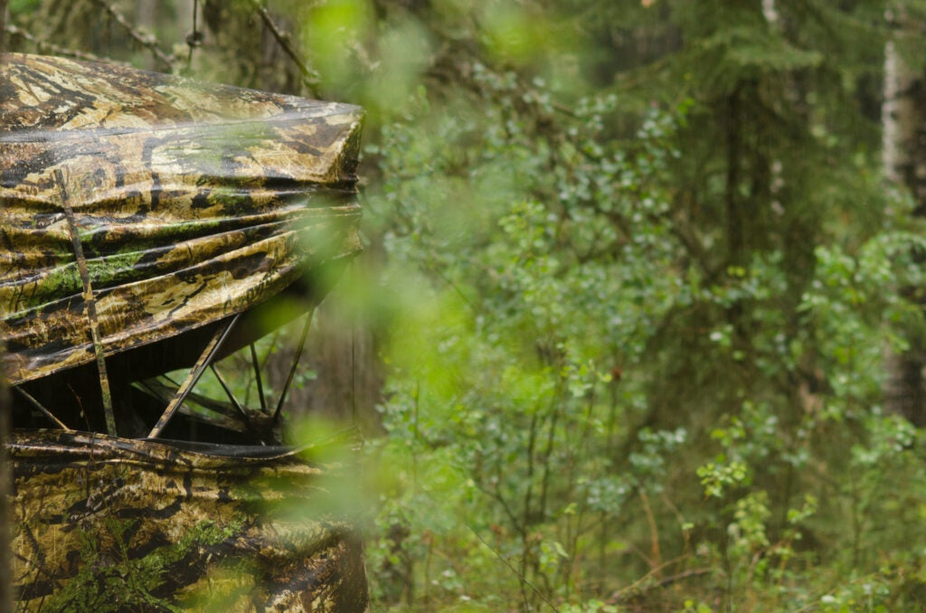A wet camo hunting ground blind sitting in the green woods.