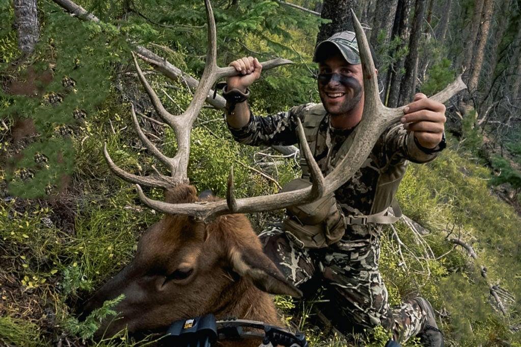A hunter kneeling behind a giant elk.