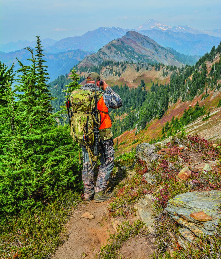 A hunter in blaze orange with a pack glassing in the mountains.