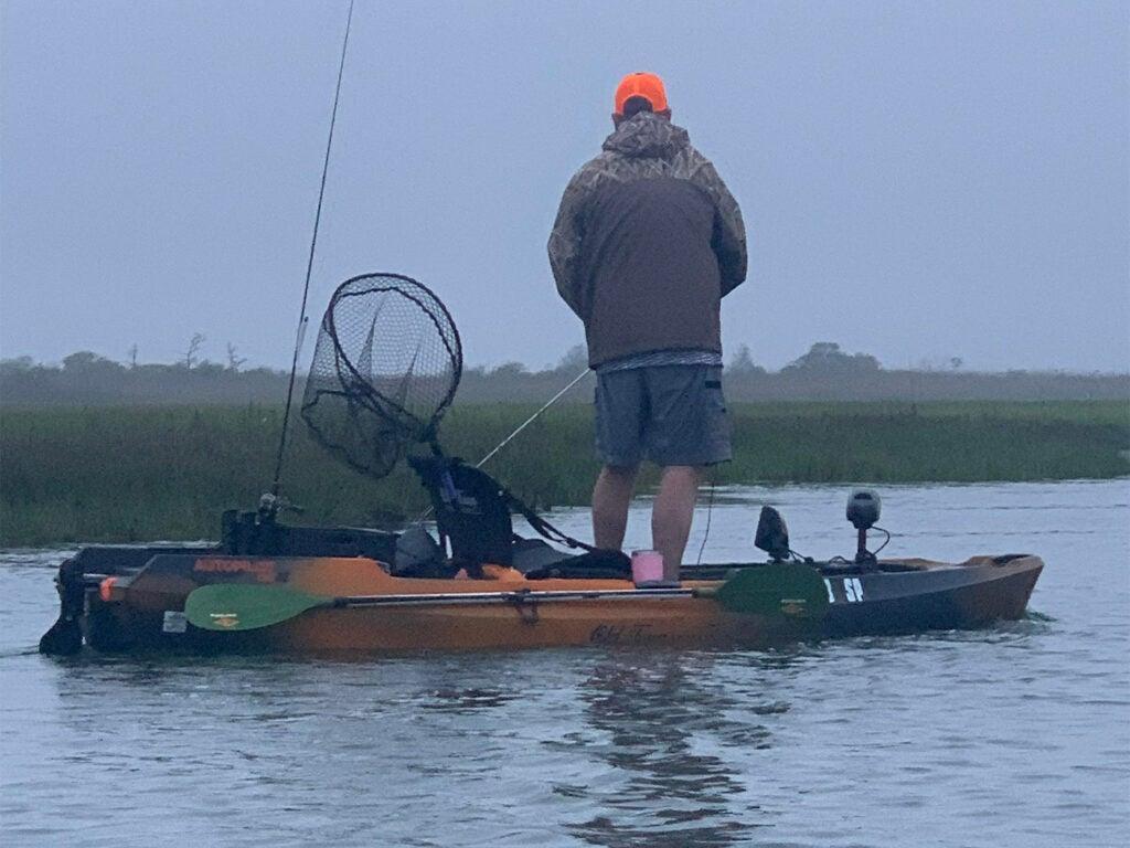 An angler fishing off of a fishing kayak.