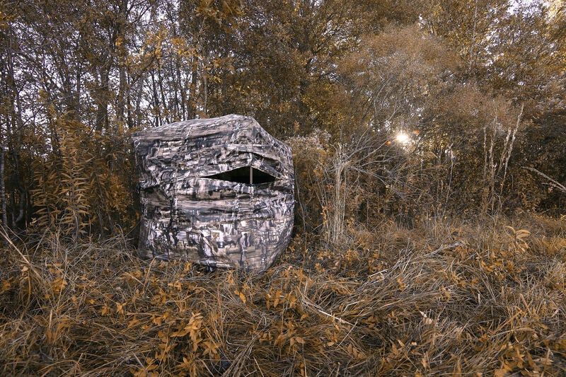 A camo Primos Double Bull Surroundview 360 groundblind on a field edge in the fall.