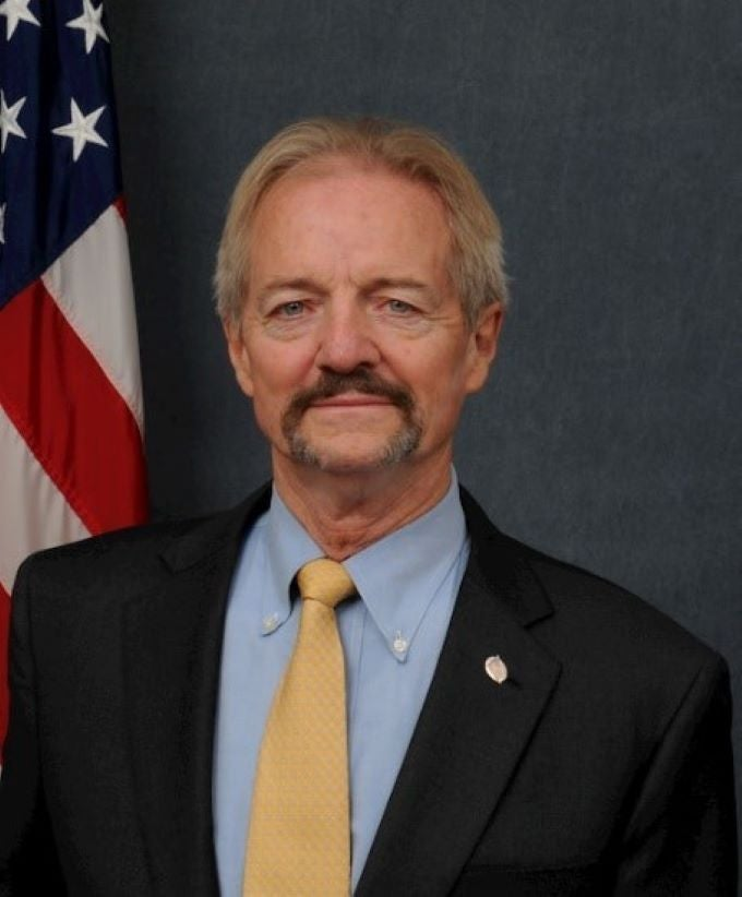 A portrait of William Perry Pendley, a white man with a mustache and goatee in a suit in front of an American flag.