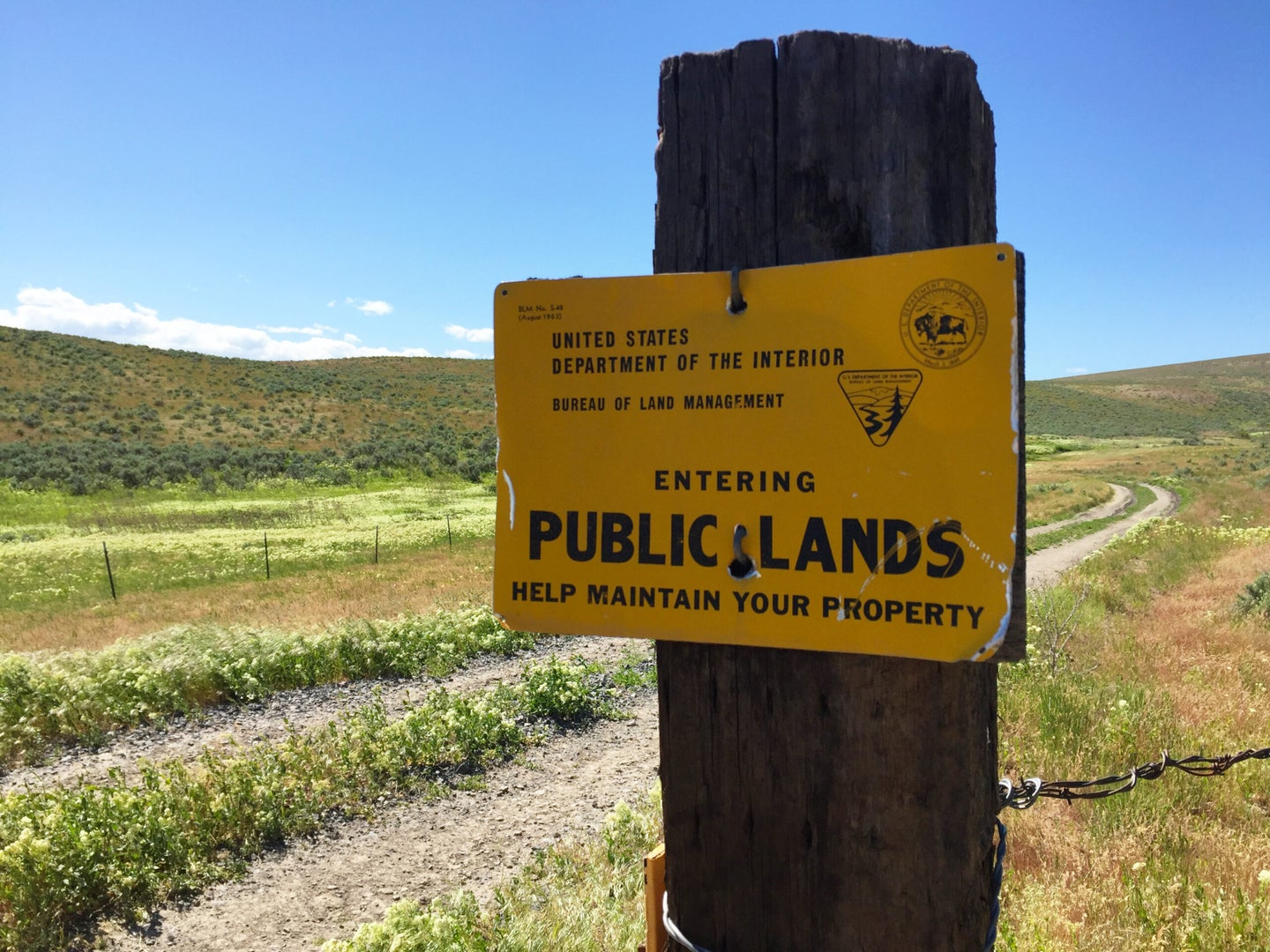 """A yellow sign that reads """"Entering Public Lands"""" on a weathered fence post in front of a two-track road"""