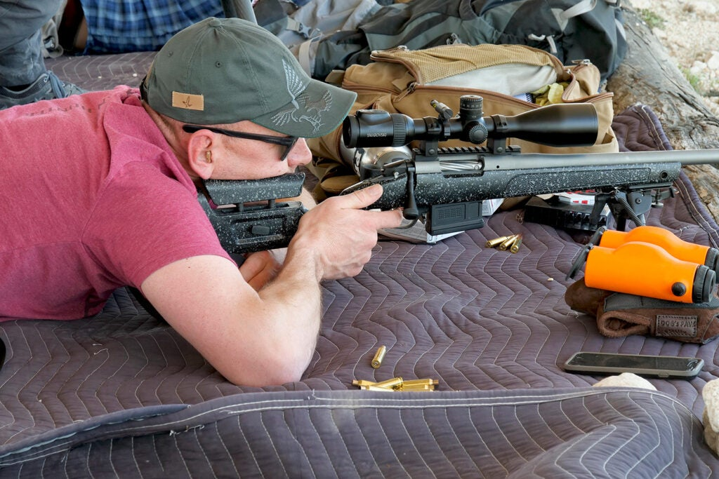 A male shooter aims a rifle at a shooting range.