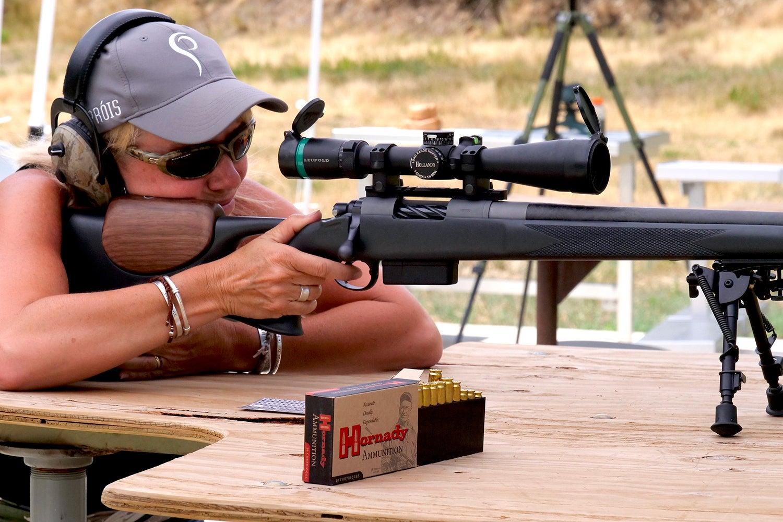 A woman rifle shooter aims a rifle at a shooting range.