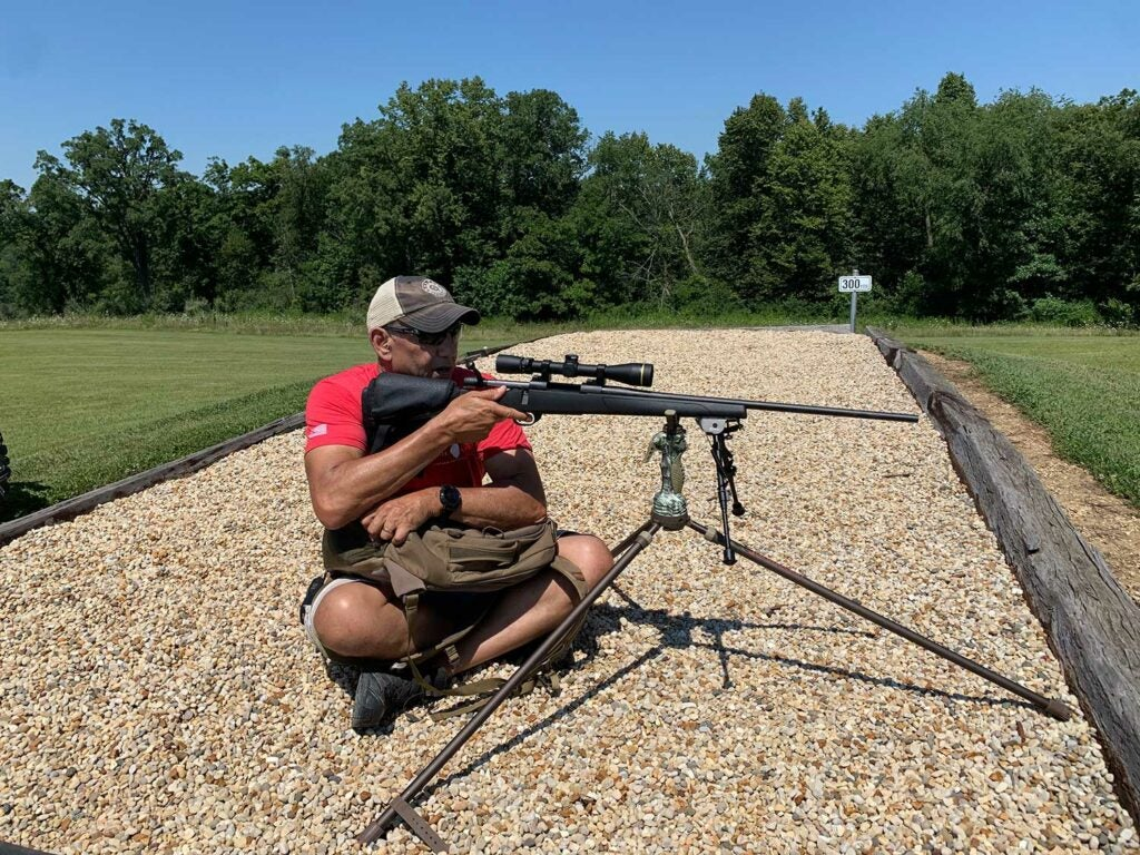 A man aiming a rifle on a shooting stick.