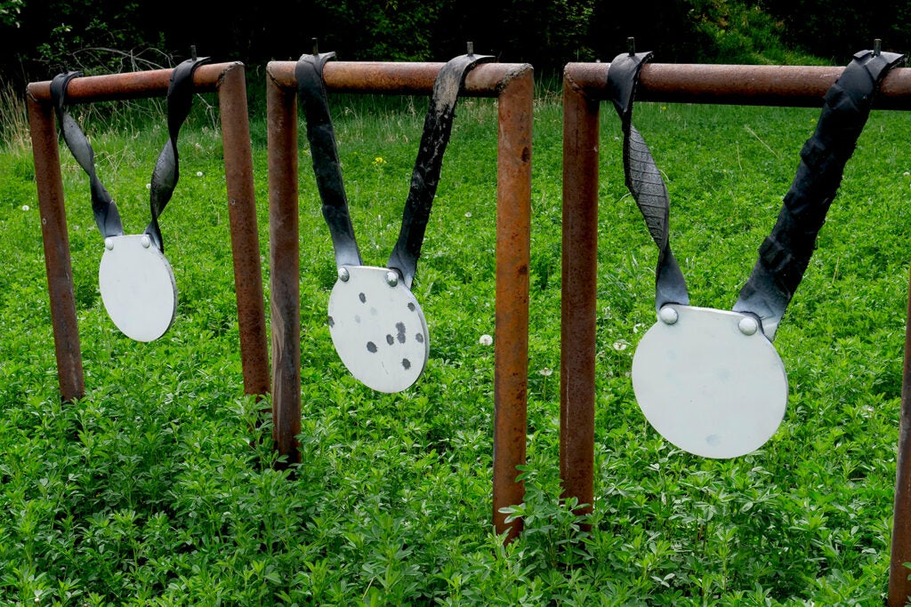 Three round metal plates hang from a metal framework to be used as shooting targets.
