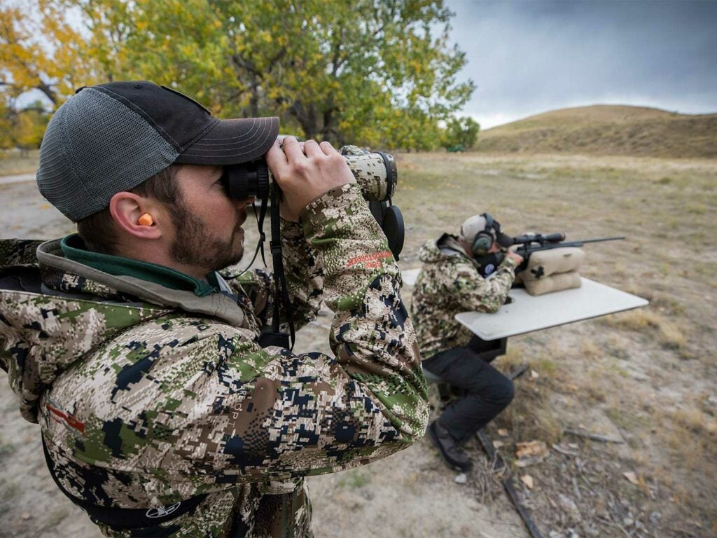 A man uses binoculars to sight a large open field.