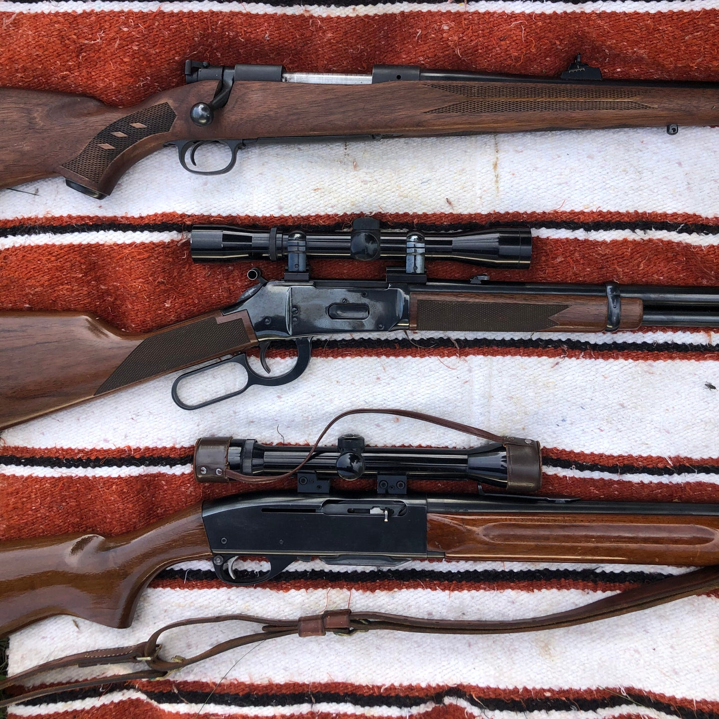 Three old rifles, two with scopes, on a woven red, white, and black blanket.