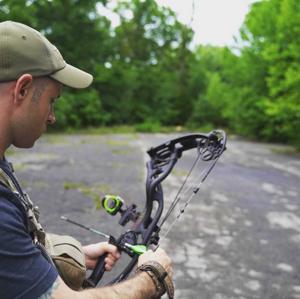 A hunter practicing bowhunting in an open wooded area.