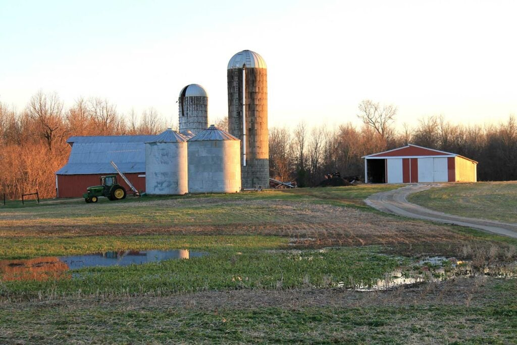 A landscape photograph showing a barn, grain silos and a tractor in a field.