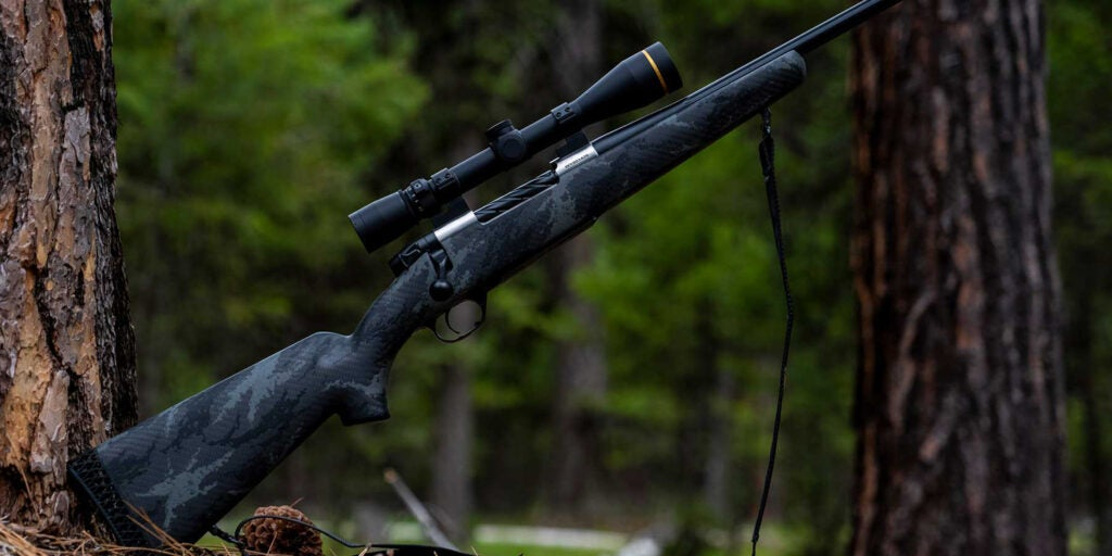 A Weatherby Ti Rifle leaning against a tree in the woods.