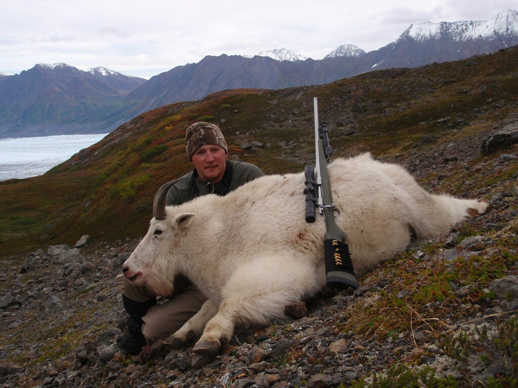 A male hunter kneeling behind a large white mountain goat.