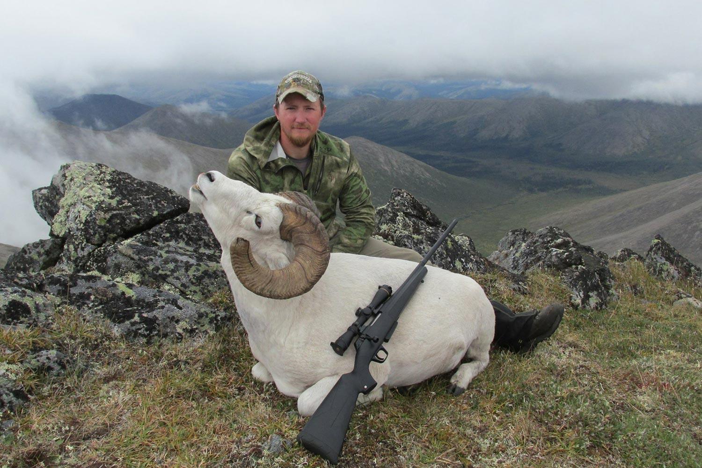 Tyler Freel kneeling behind a large white mountain goat.