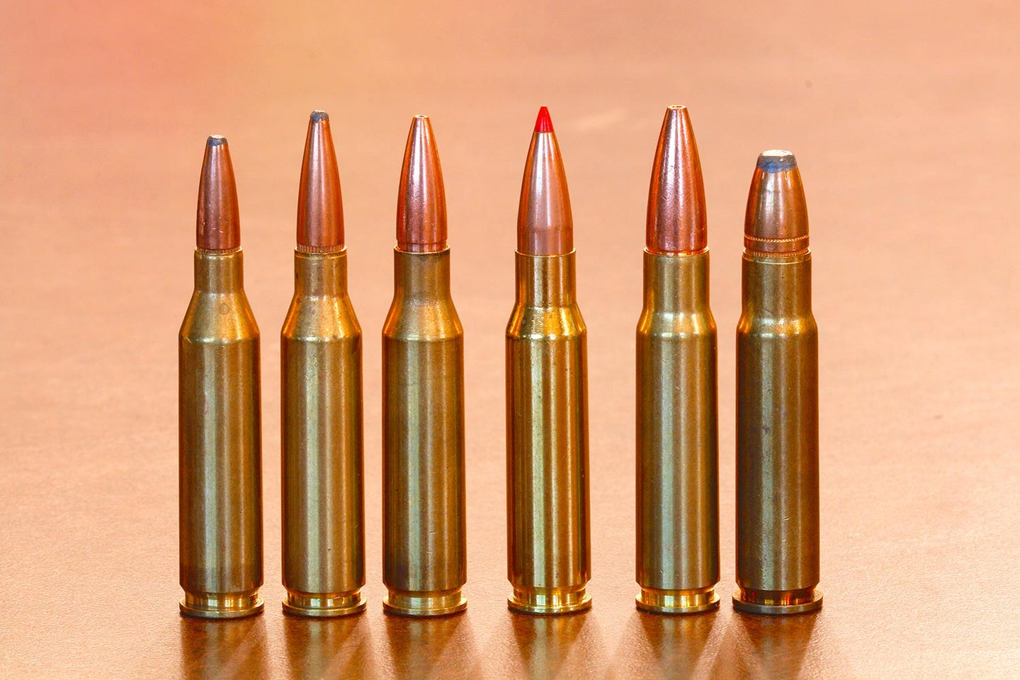 A lineup of rifle cartridges on a table.