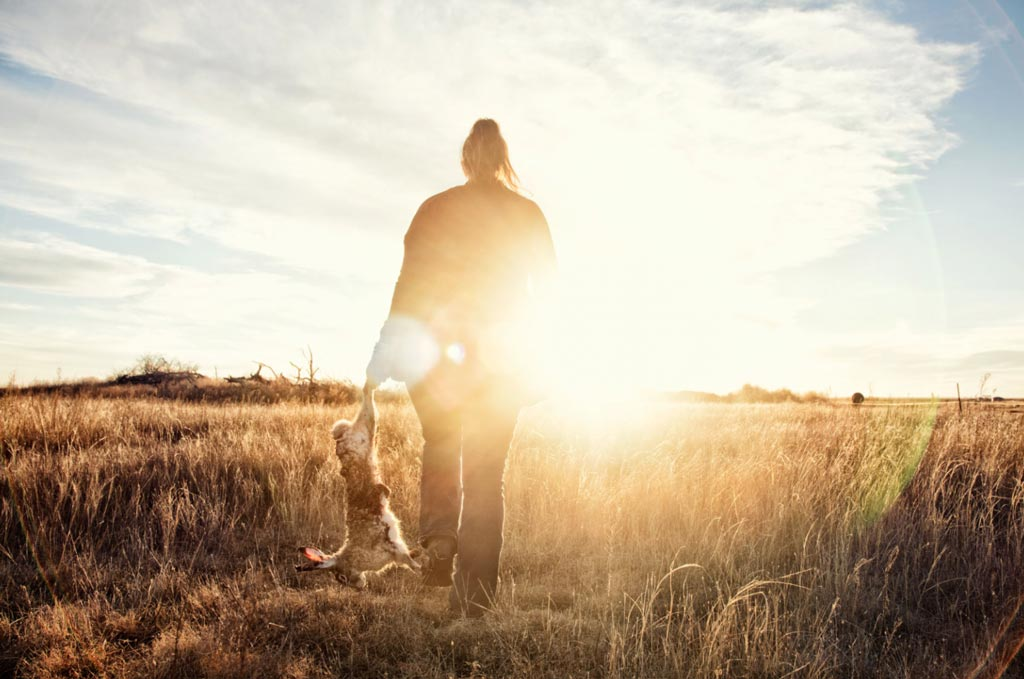 A woman walks in an open field with the sunset in the horizon.