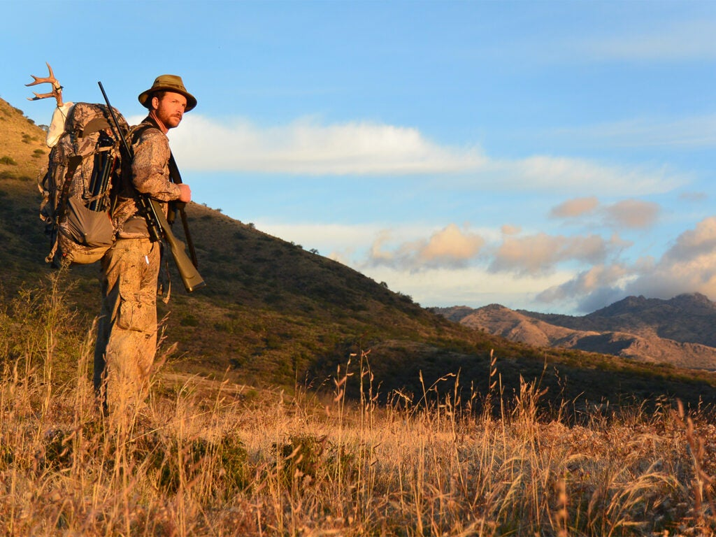 A man with a rifle and backpack in a large hillside.