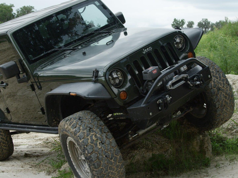 A black Jeep driving across rough terrain.