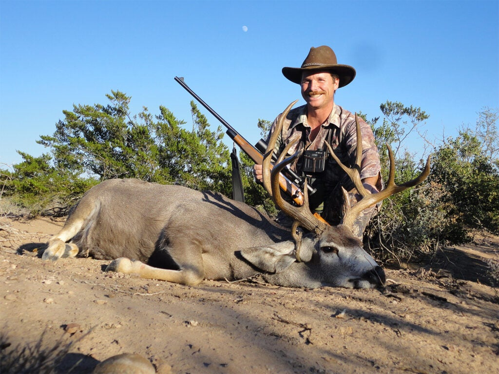 A man wearing a cap kneels behind a deer  in the dirt.