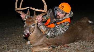 A hunter in camo with a large 8-point whitetail buck.