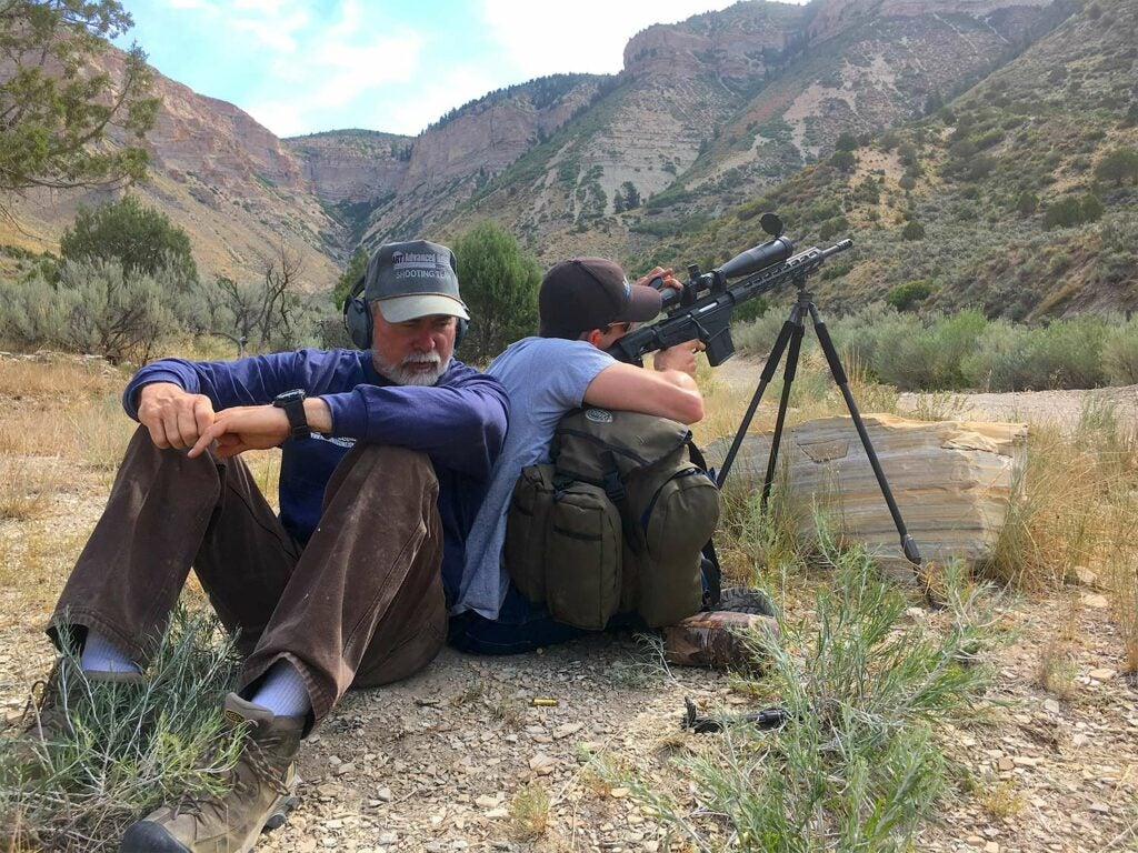 Two men sit back-to-back while one aims a rifle.
