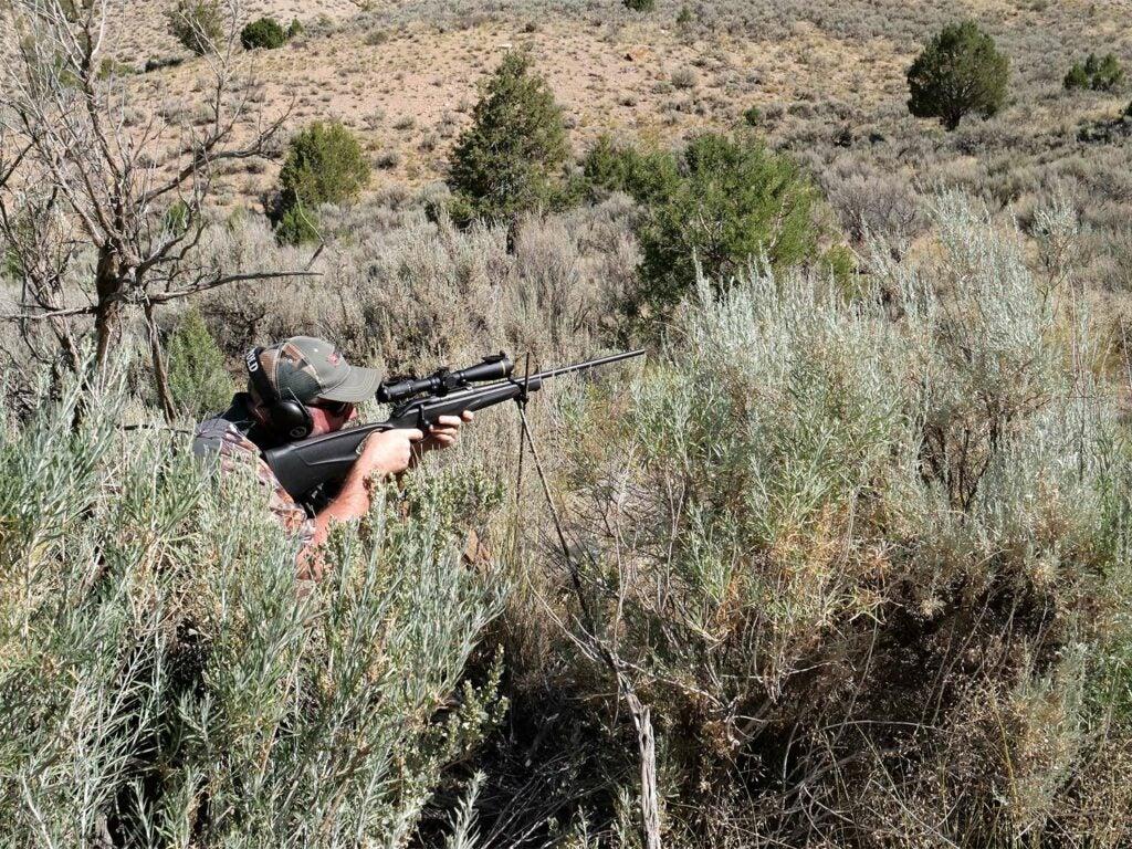 A concealed hunter inn camo aims a rifle in a field.